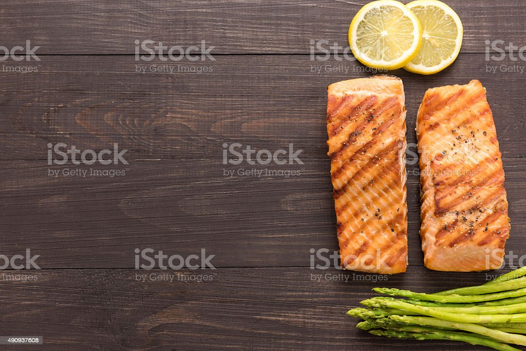 Grilled salmon with lemon, asparagus on wooden background stock photo