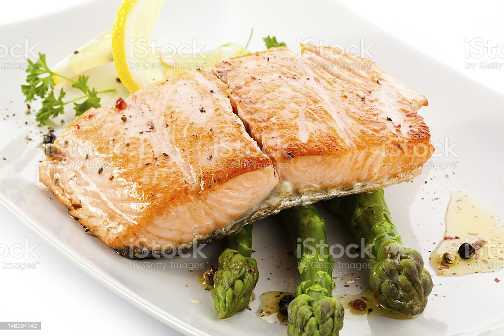 Grilled salmon with lemon served on asparagus spears stock photo