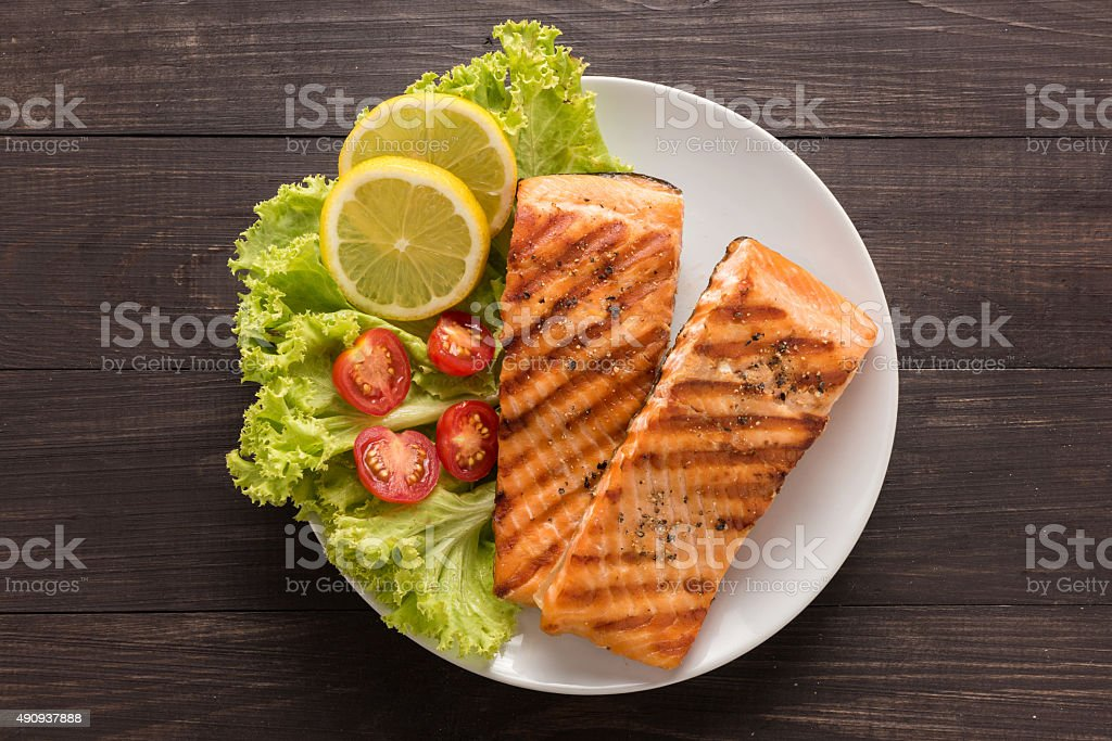 Grilled salmon with lemon,tomato on the wooden background stock photo