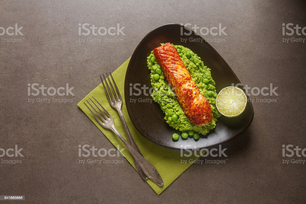 Grilled salmon with pea puree on a brown plate. Gray background. stock photo