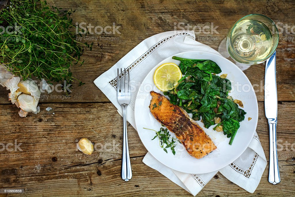 grilled salmon with spinach and white wine on dark wood stock photo