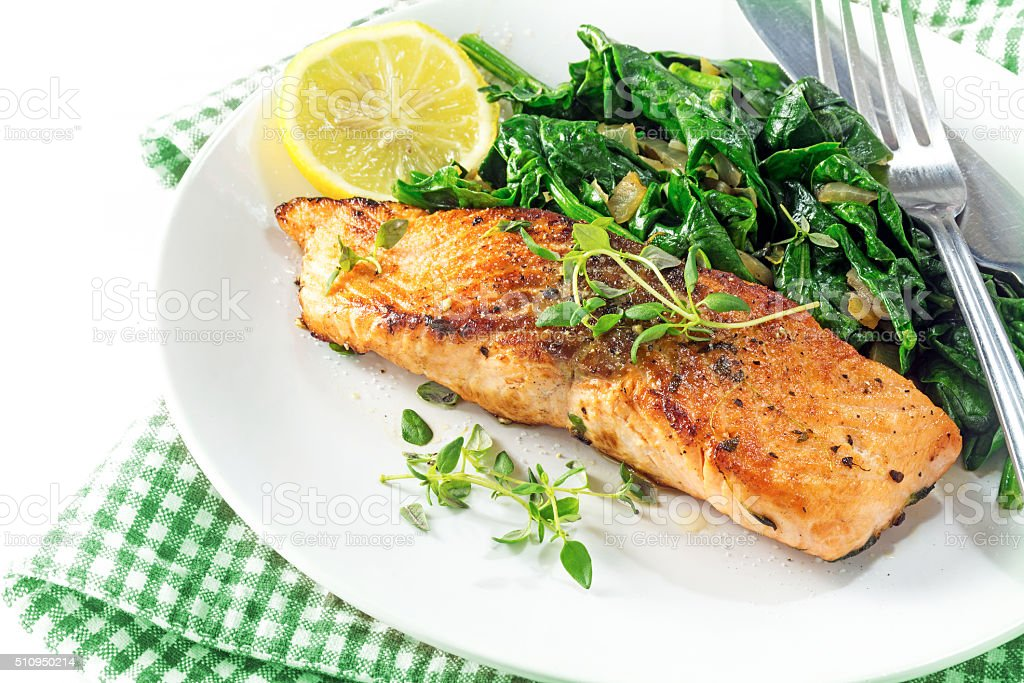 grilled salmon with thyme, lemon and spinach, vegetarian food stock photo