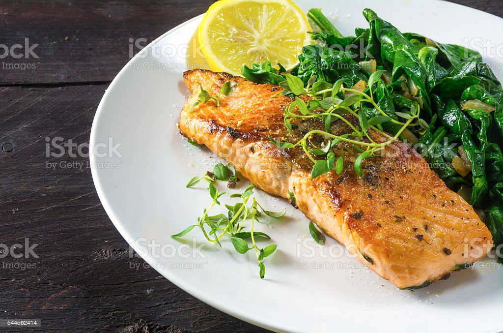 grilled salmon withspinach on a white plate, dark wooden table stock photo