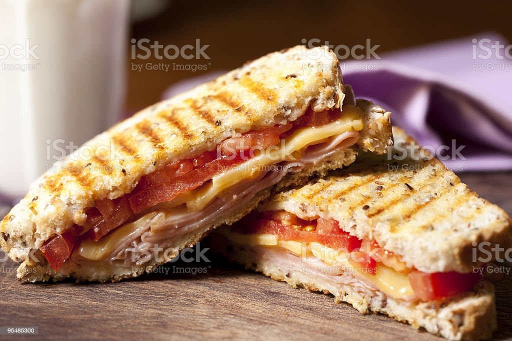 Grilled sandwich sliced in half in wooden table stock photo