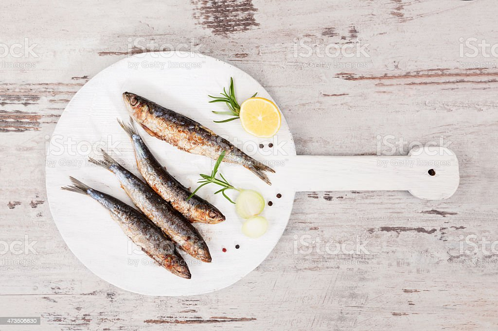 Grilled sardines on wooden plate. stock photo