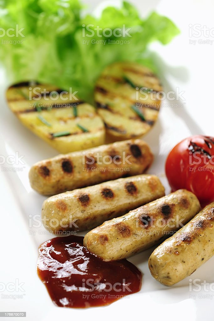 Grilled sausage and potatoes with ketch-up stock photo