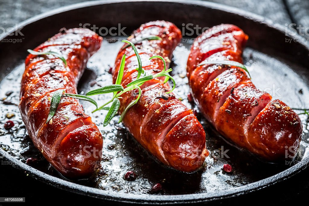 Grilled sausage with fresh rosemary on hot barbecue dish stock photo