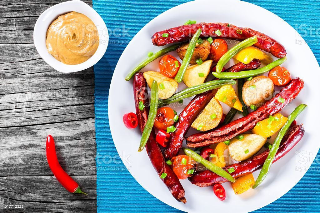 Grilled sausage with garlic, potato, cherry tomatoes, green beans, top-view stock photo