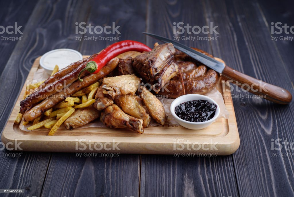 Grilled sausages and chicken with fries on a wooden board stock photo