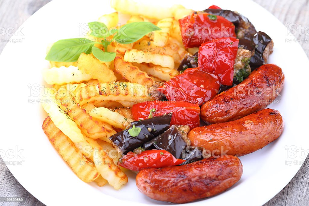 Grilled sausages and fried potatoes stock photo