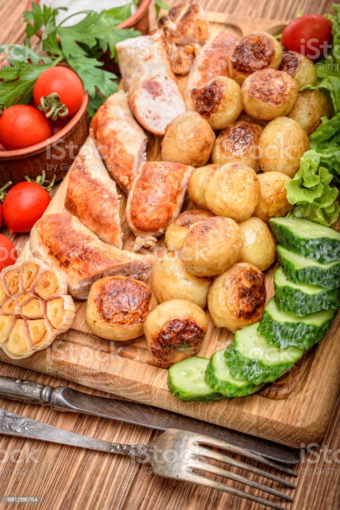 Grilled sausages and vegetables on the wooden board. stock photo