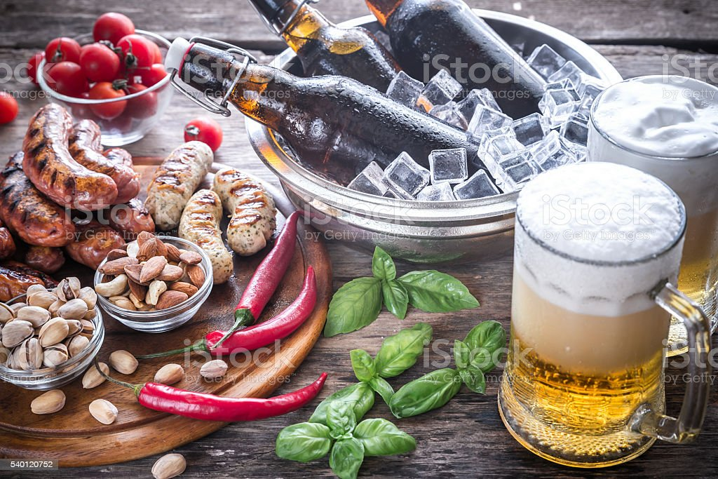Grilled sausages with appetizers and mugs of beer stock photo