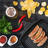 Grilled sausages with beer, chips and croutons.