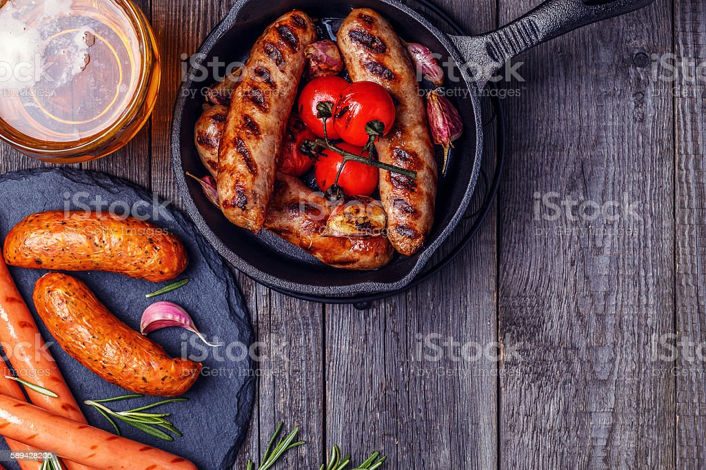 Grilled sausages with glass of beer on wooden table. stock photo