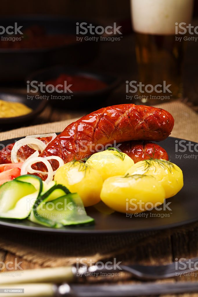 Grilled sausages with onions, served with boiled potato stock photo