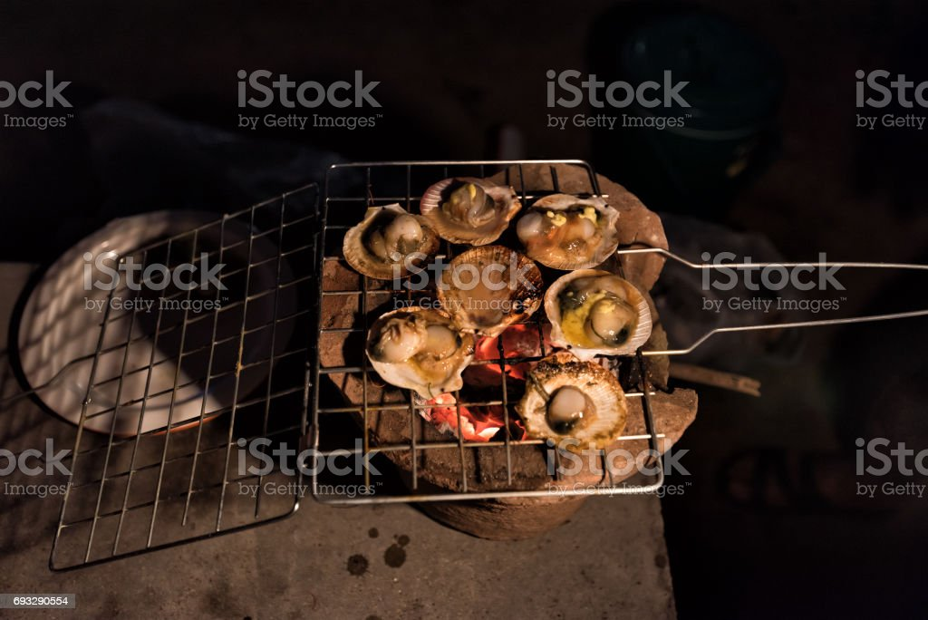 Grilled scallop on charcoal stove camping at campfire. stock photo