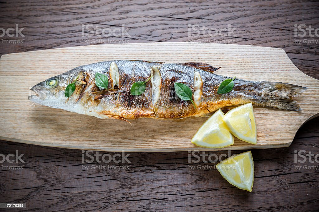 Grilled seabass on the wooden board stock photo