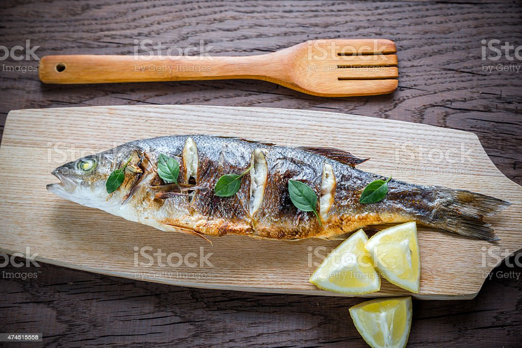 Grilled seabass with lemon on the wooden board stock photo
