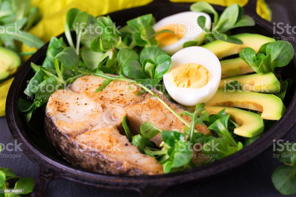 Grilled sheatfish fish steak with avocado, arugula and salad stock photo