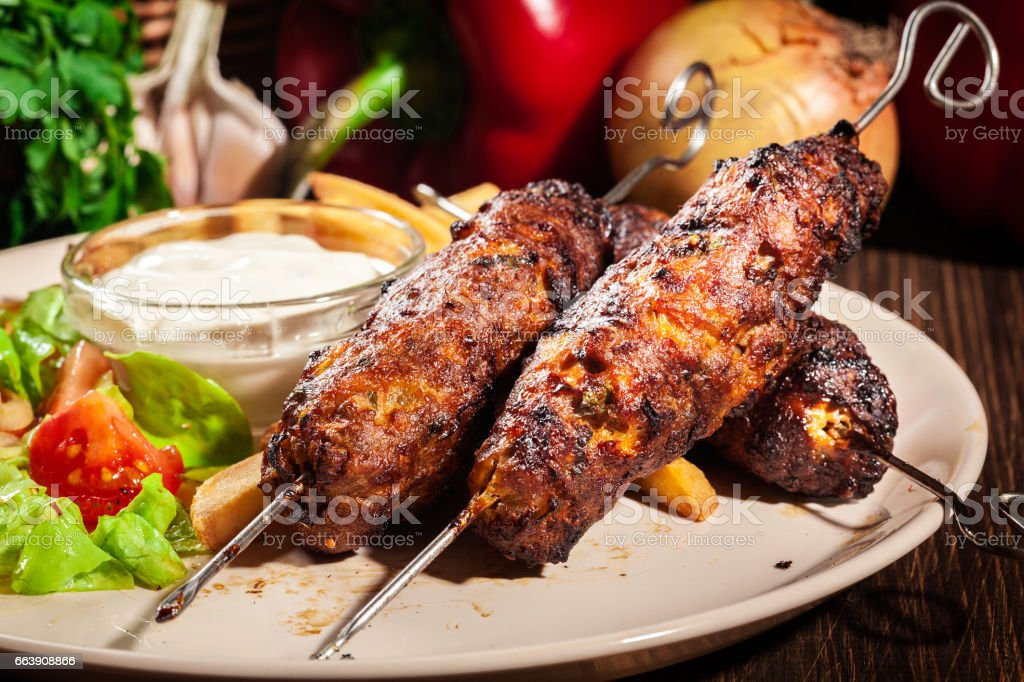 Grilled shish kebab served with fried chips and salad stock photo