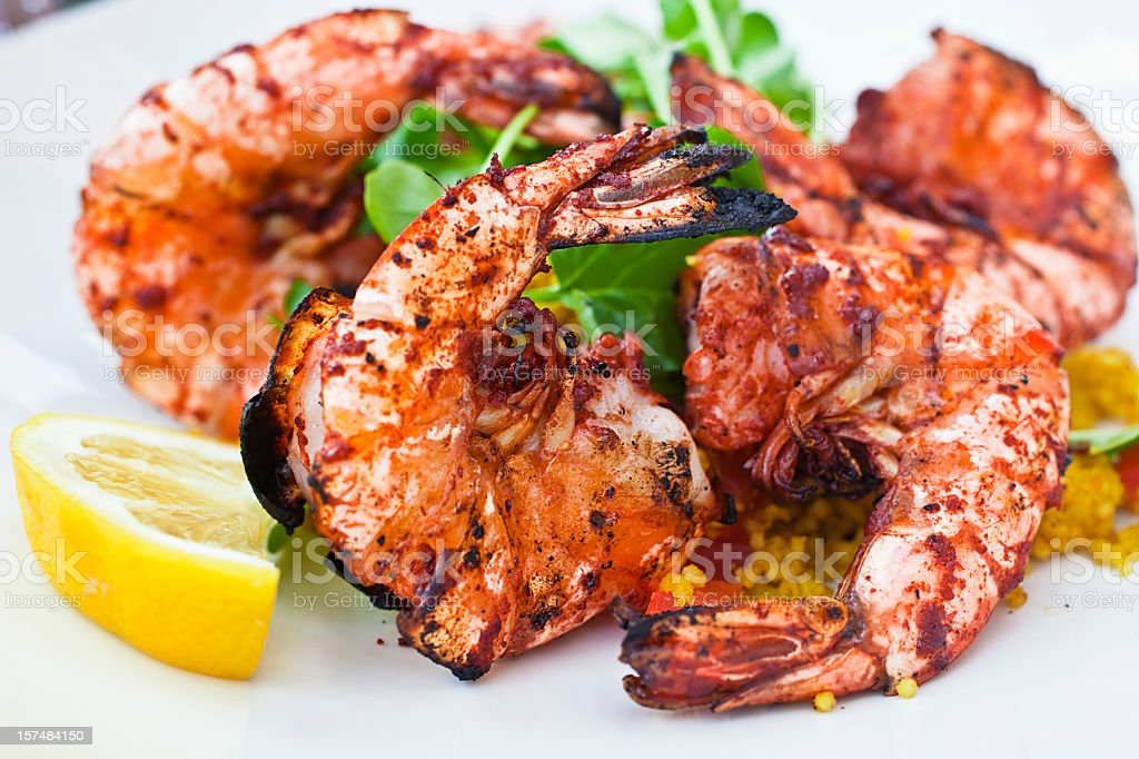 Grilled shrimp on a bed of couscous with a lemon wedge  stock photo