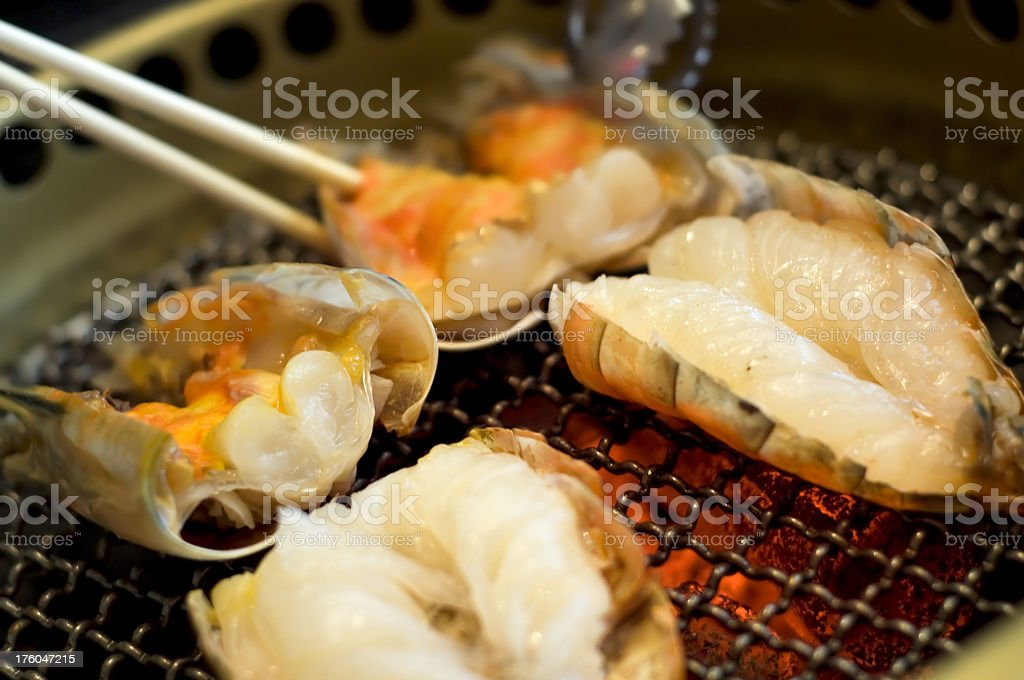 Grilled shrimp on barbecue grill with chopstick , hot fire royalty-free stock photo