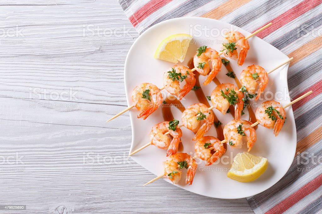 Grilled shrimp on skewers with lemon horizontal top view stock photo