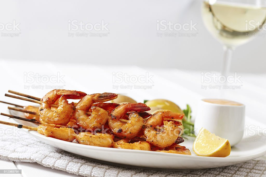 Grilled shrimp on skewers with potatoes and sauce stock photo