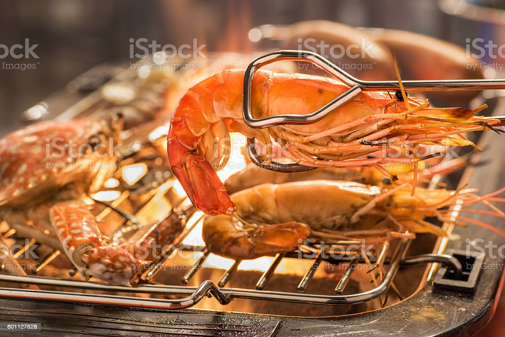 grilled shrimps on the flaming grill with flame stock photo