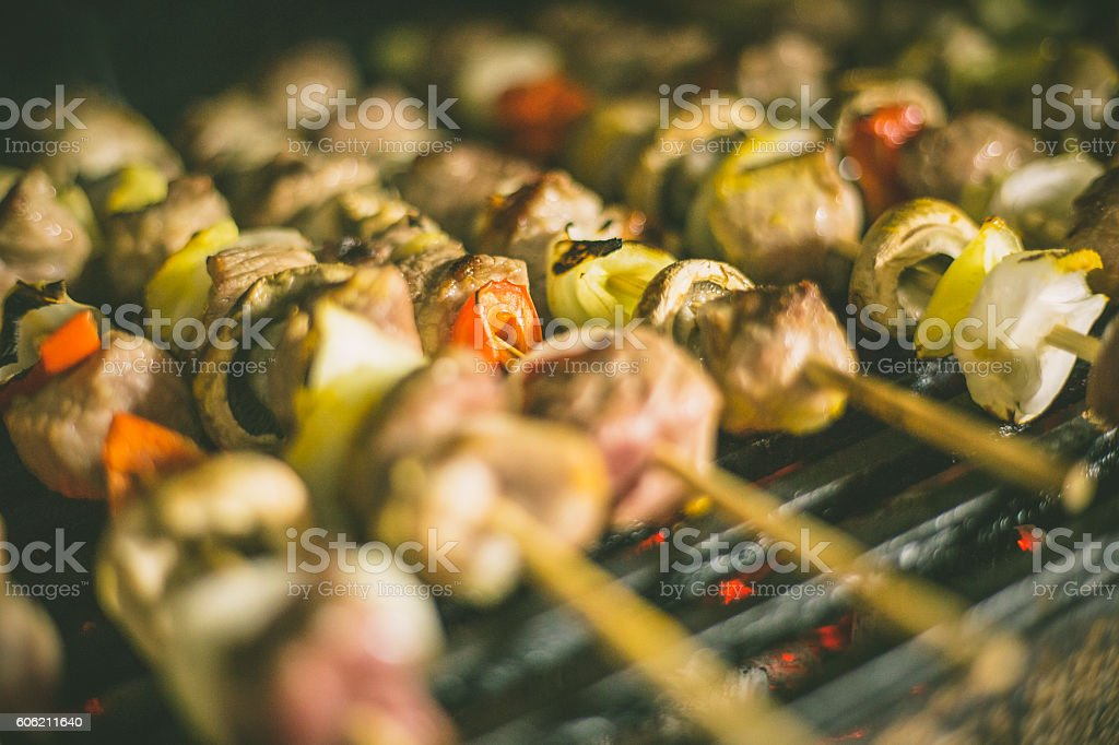 Grilled Skewers of sausage, mushrooms and onion on grill stock photo