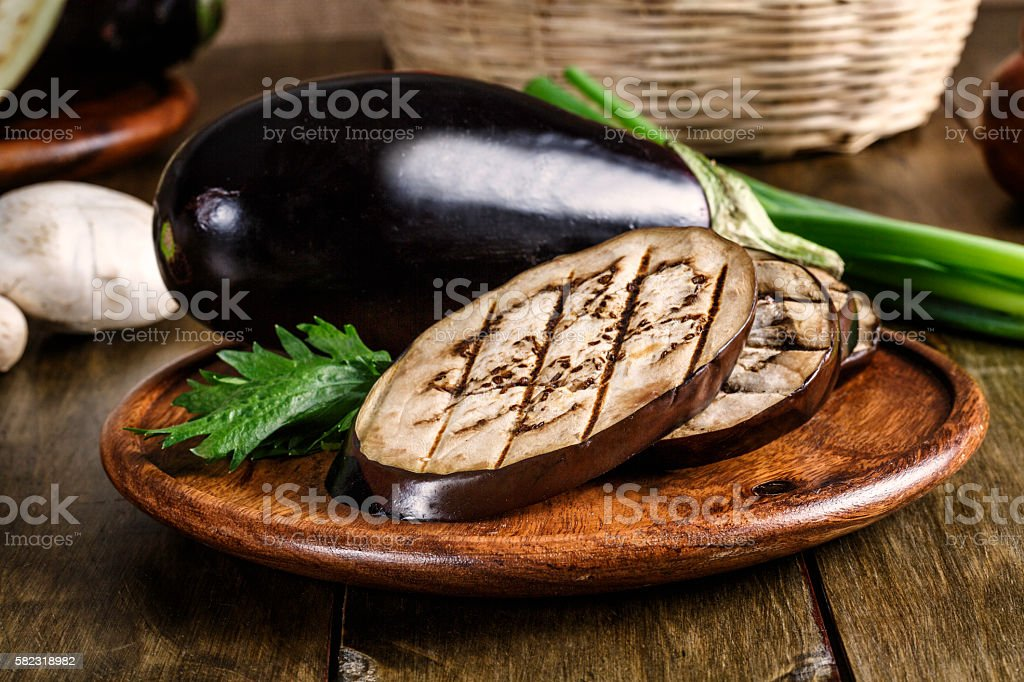 Grilled slices of Eggplant on wooden plate stock photo