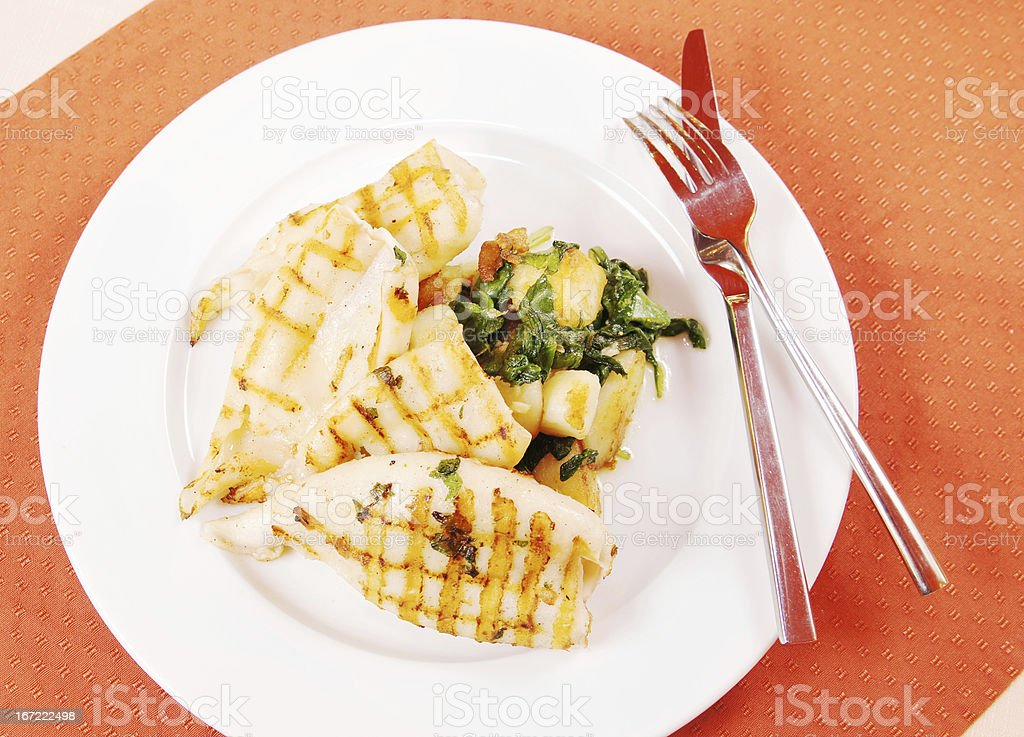 Grilled squids and potato on a white plate royalty-free stock photo