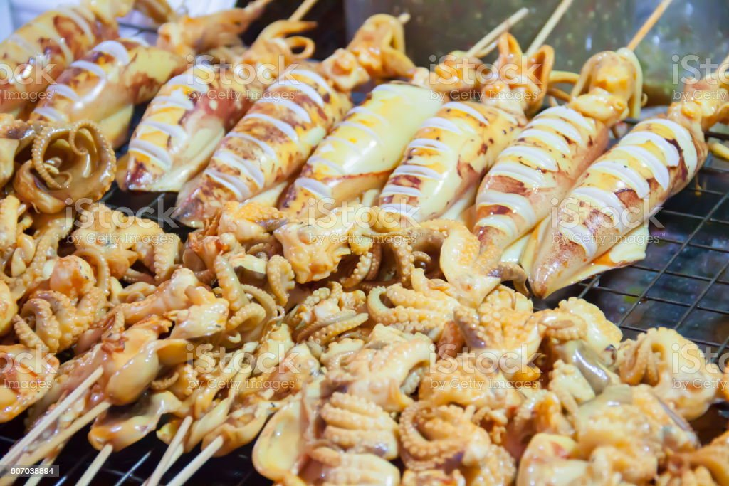 Grilled squids sold on the street market in thailand stock photo