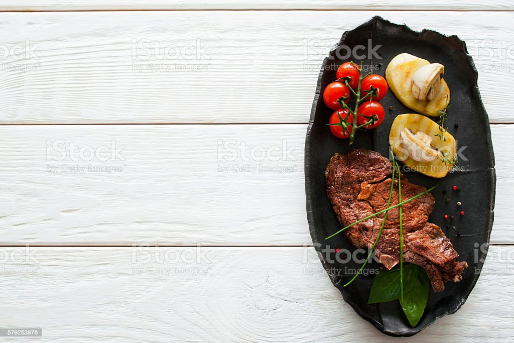 Grilled steak and potato, white wood, copyspace stock photo