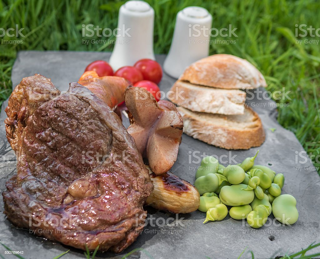 Grilled steak and sausages at a spring picnic stock photo