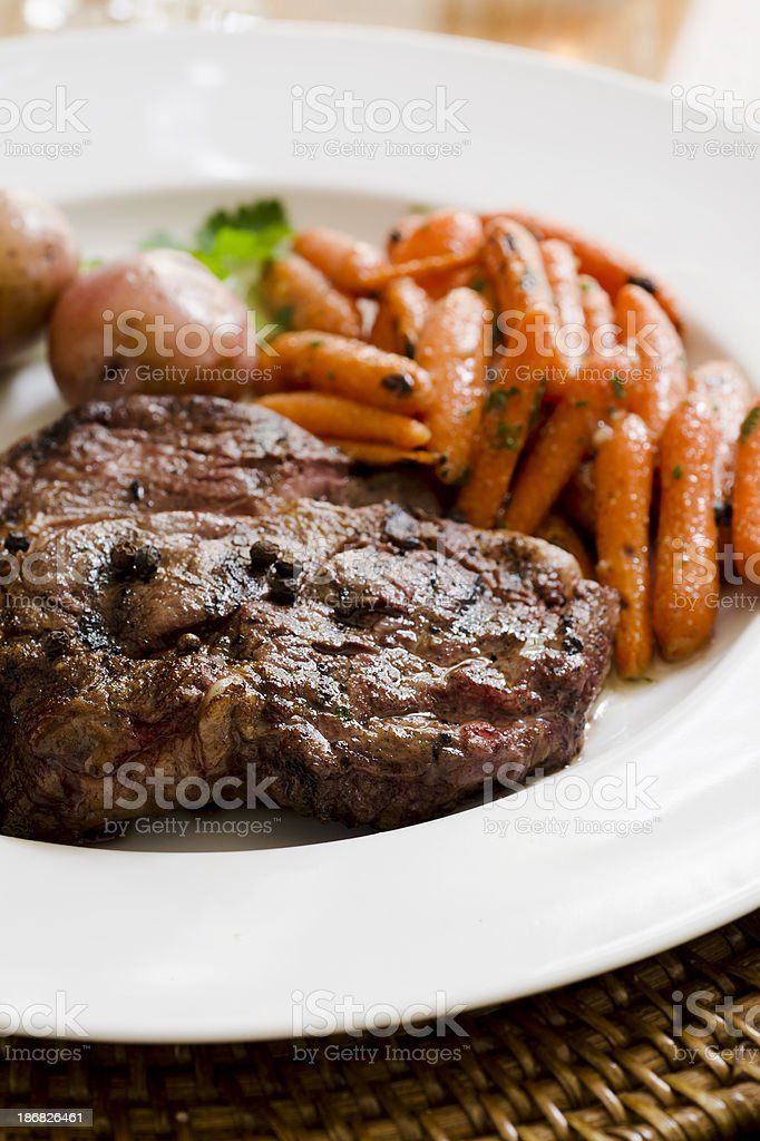 Grilled Steak, Baked Potatoes, and Baby Carrots royalty-free stock photo