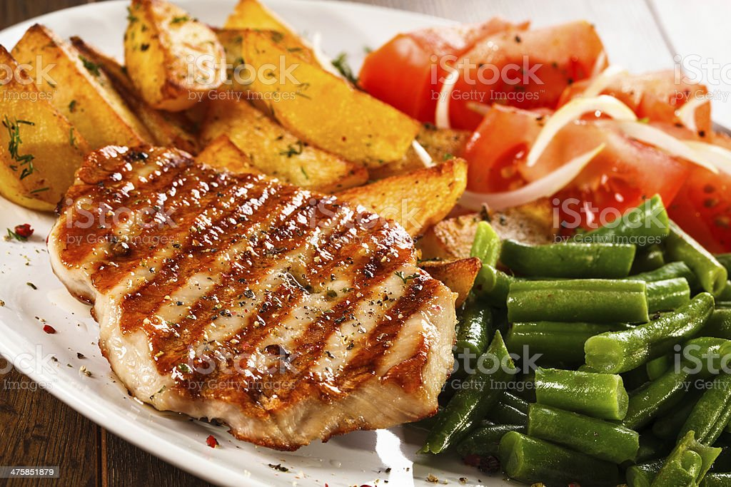Grilled steak, baked potatoes and vegetables stock photo