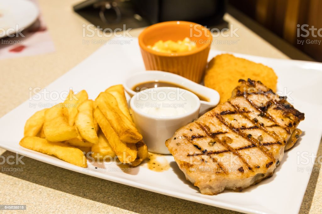Grilled steak, French fries on the white plate. stock photo