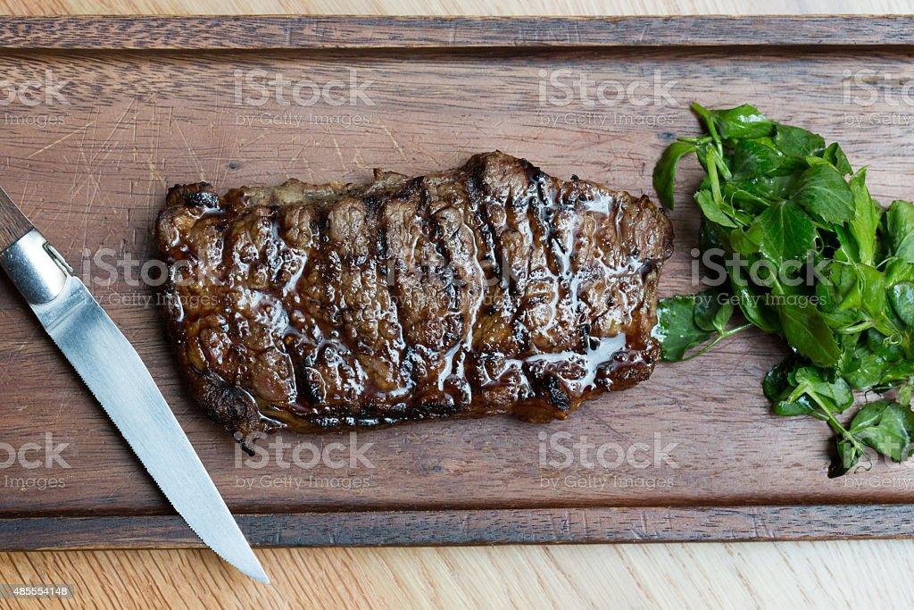 Grilled Steak on Wooden Board stock photo