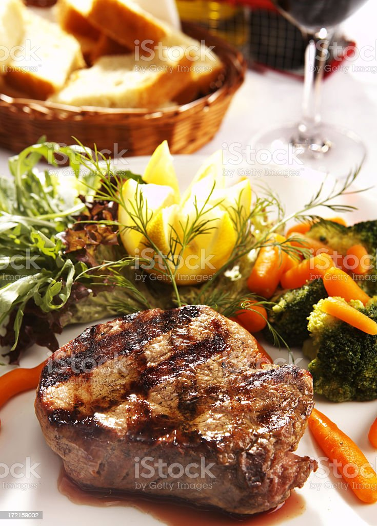 Grilled steak plated with vegetables with bread and wine royalty-free stock photo