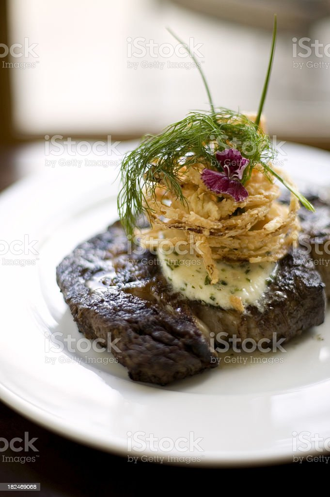 Grilled steak topped with crispy fried onions and herb butter stock photo