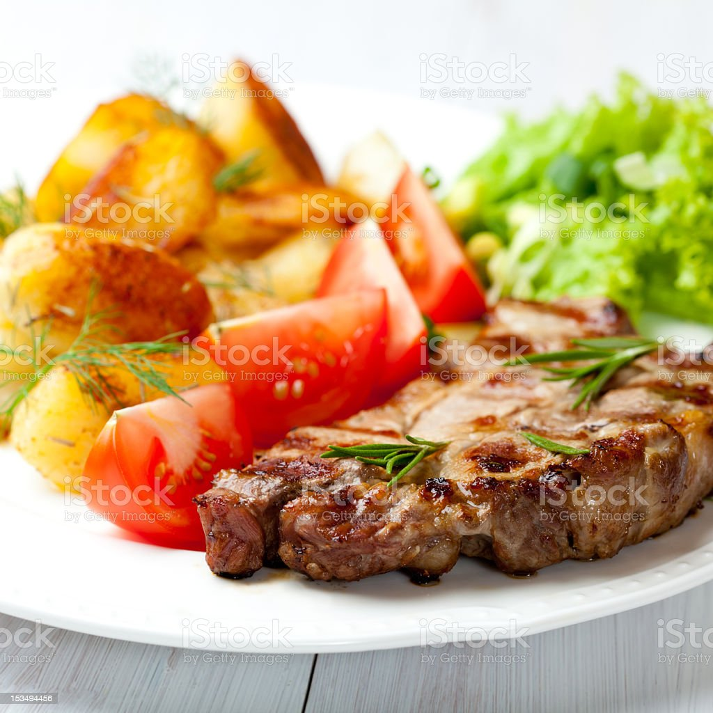 Grilled steak with baked potatoes and fresh vegetables royalty-free stock photo