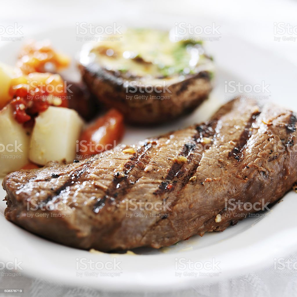 grilled steak with potatoes and stuffed mushroom stock photo
