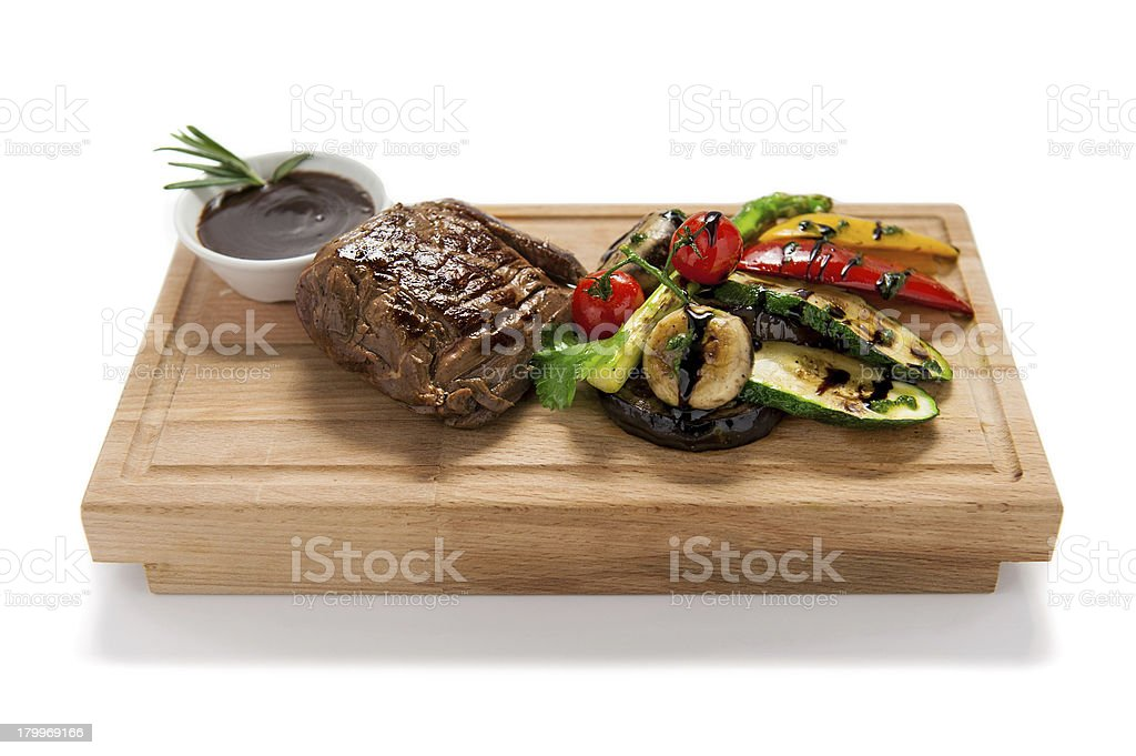 Grilled steak with vegetables on a wooden board royalty-free stock photo