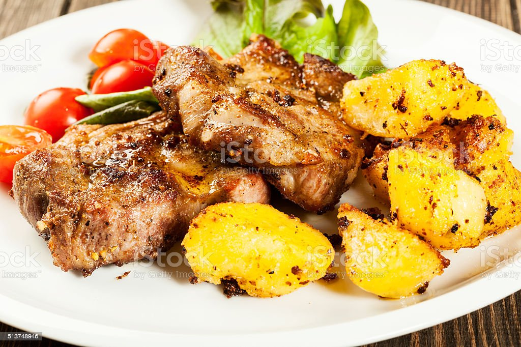 Grilled steaks and baked potatoes stock photo