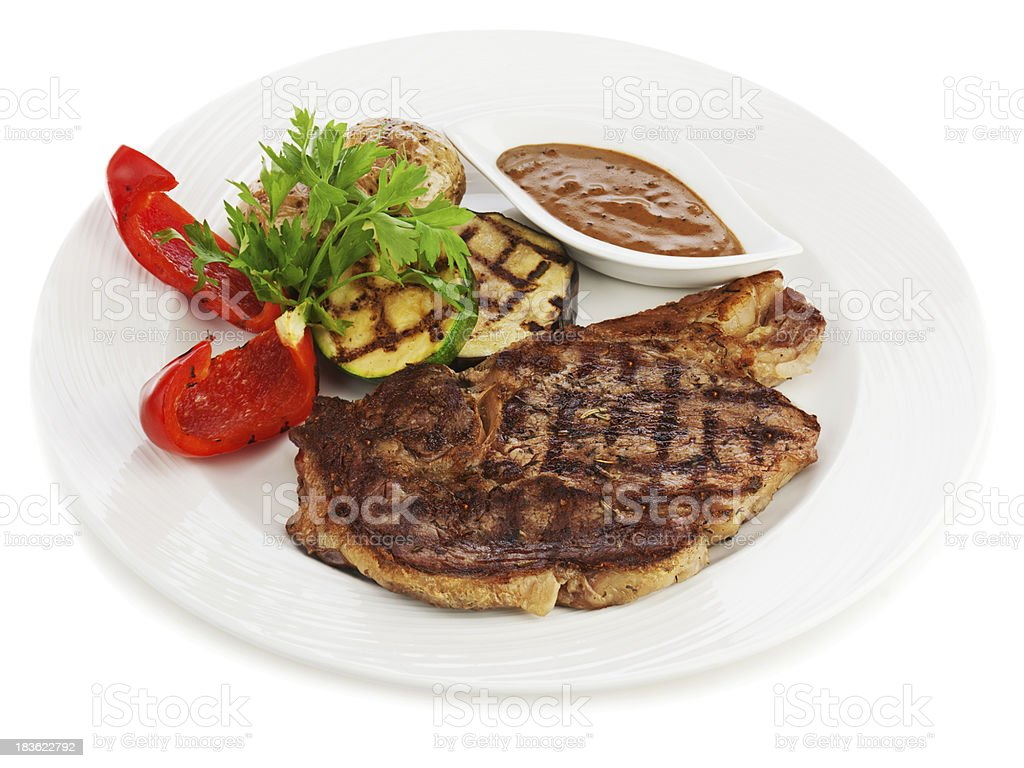 Grilled steaks, baked potatoes and vegetables on white plate. royalty-free stock photo