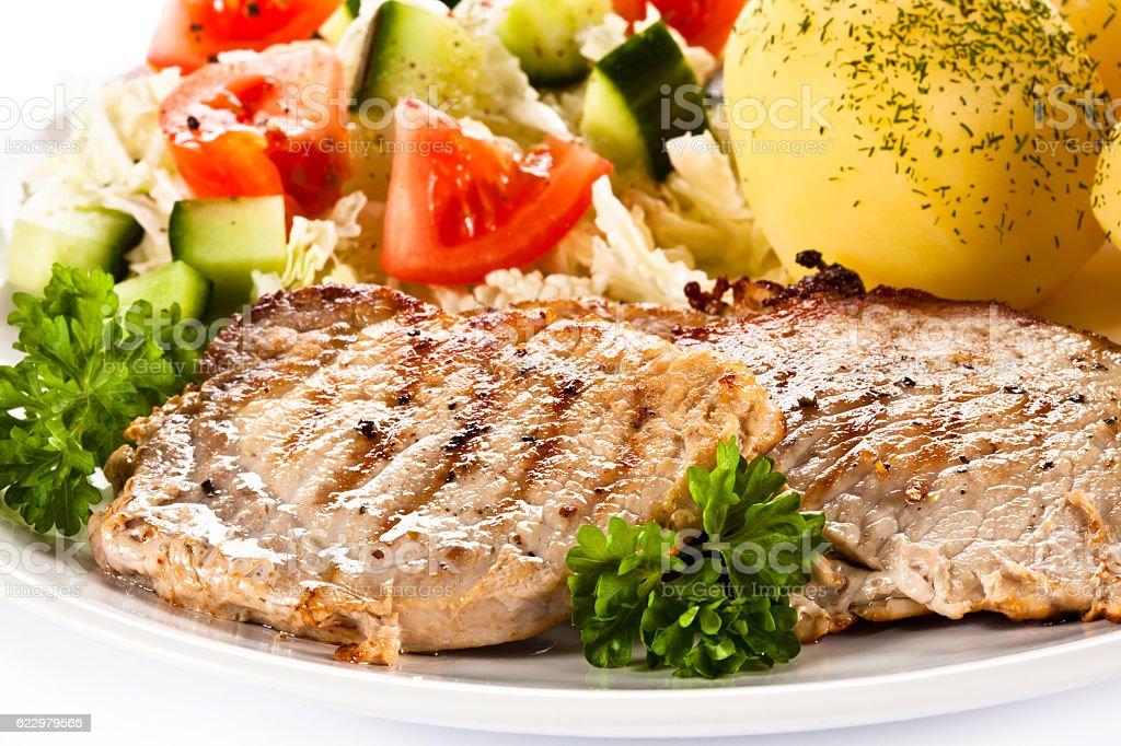 Grilled steaks, boiled potatoes and vegetables stock photo