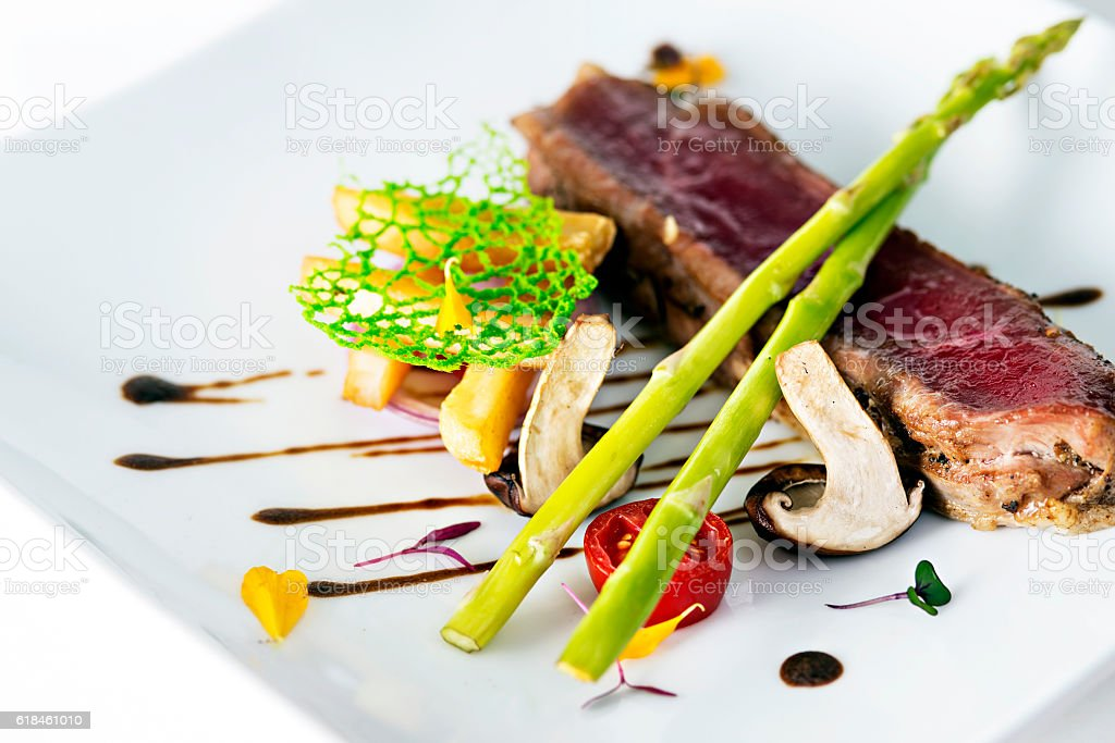 Grilled steaks on white dish in restaurant stock photo