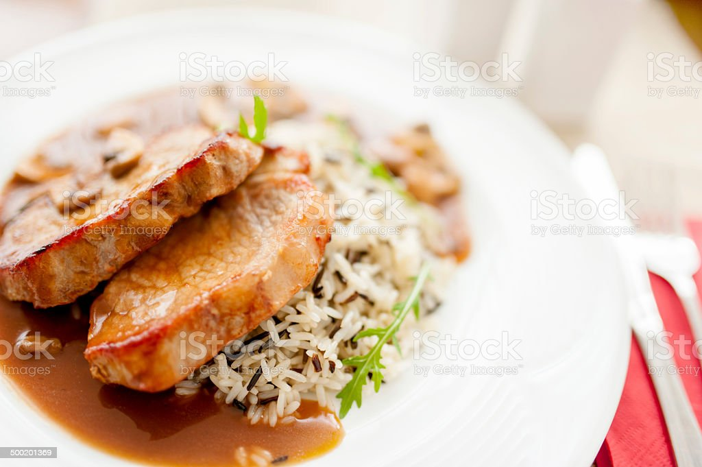 grilled suculent pork chop and rice as main course stock photo