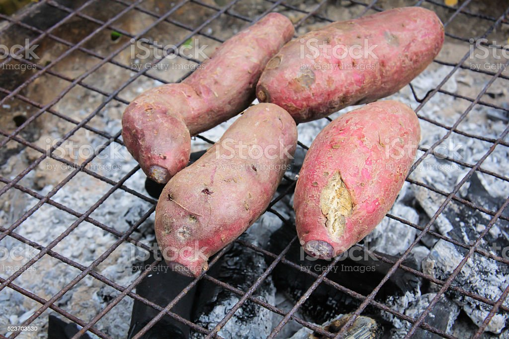 grilled sweet potato on charcoal grill stock photo